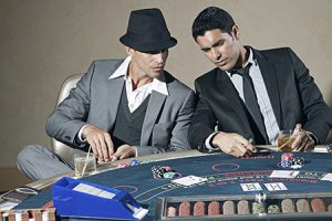 men cheating at a poker table